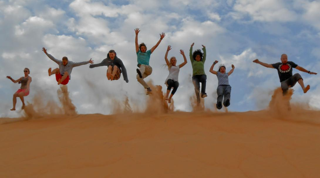 Volunteers jumping on the hill of the dunes in Senegal shooting sand into the air for an epic photo